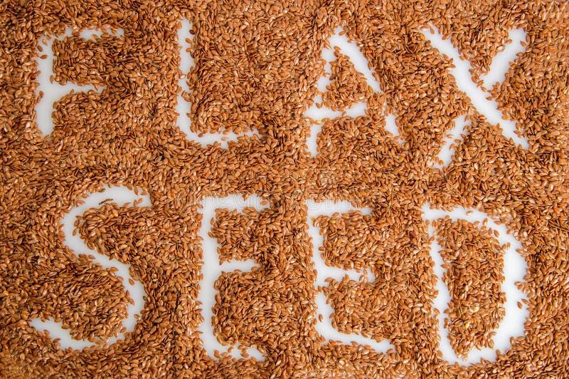 Odgórny widok Powierzchnia rozsypisko flaxseeds Podpis: Flaxseed Biały tło Zamyka up, makro- obraz stock