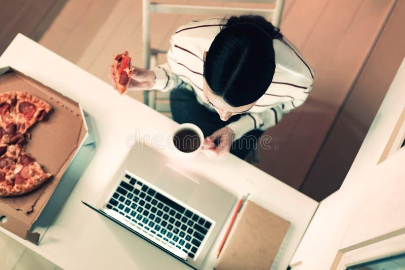 Odgórny widok pracowity kobiety obsiadanie przy stołem zdjęcie royalty free