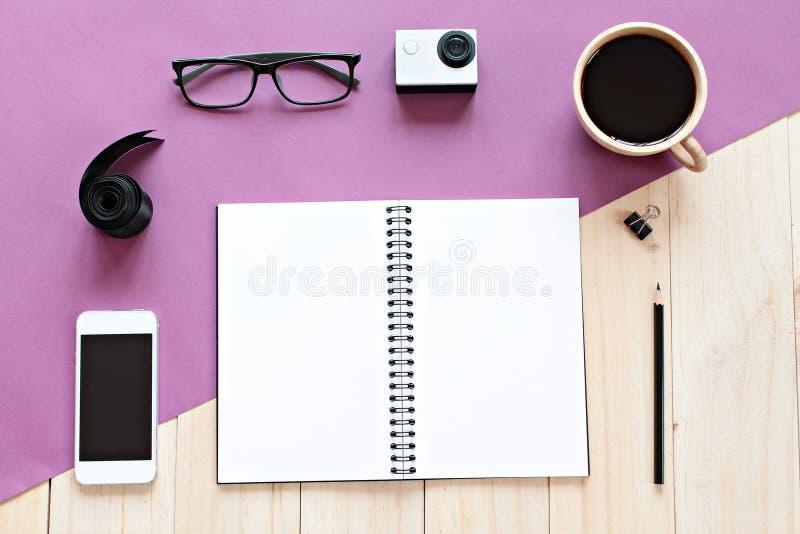 Odgórny widok pracujący biurko z pustym notatnikiem z ołówkiem, filiżanką, eyeglasses, telefonem komórkowym i akci kamerą na drew obraz royalty free
