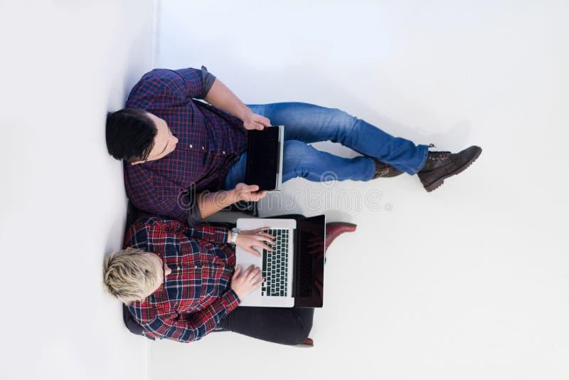 Odgórny widok pracuje na laptopie przy początkowym biurem para fotografia stock