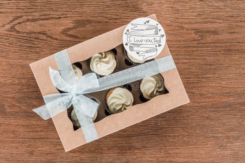 odgórny widok pudełko z smakowitymi babeczkami w pudełku z kocham ciebie tata kartka z pozdrowieniami, Szczęśliwi ojcowie zdjęcie stock