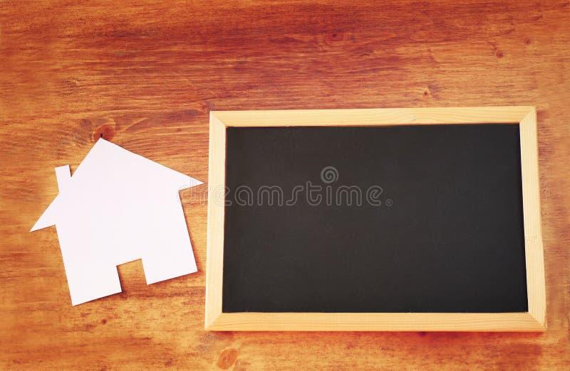 Odgórny widok pusty blackboard z pokojem dla teksta i dom kształtującego papieru cięcia nad drewnianym stołem obrazy stock