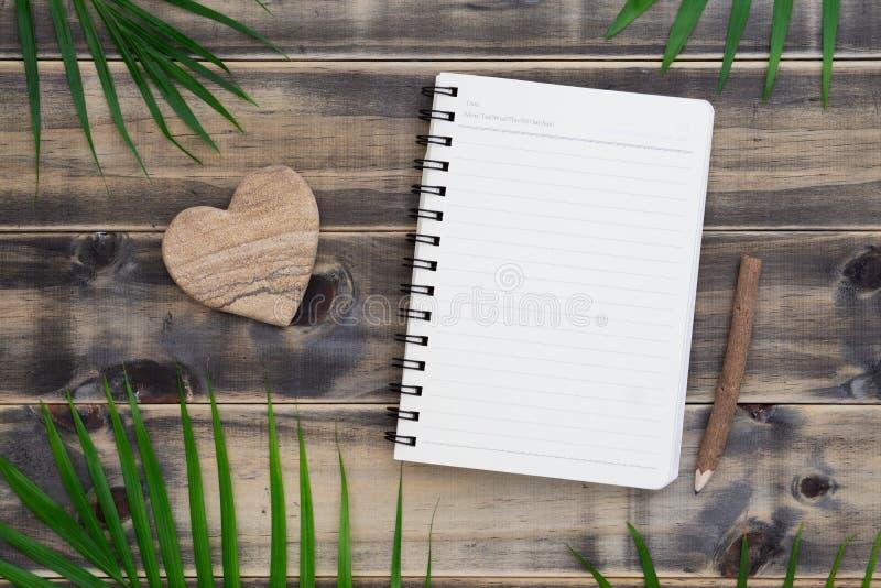 Odgórny widok pusty notatnik z palmowym liściem i kierowym kształta kamieniem na drewnianym tle, mieszkanie kłaść z kopii przestr zdjęcia stock