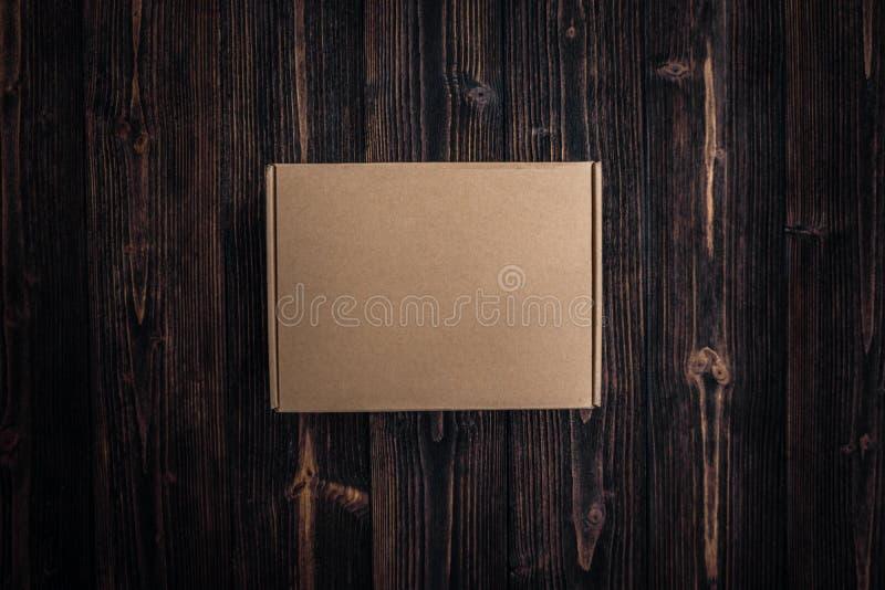Odgórny widok pusty pakunku brązu karton lub taca na drewnianym zdjęcia royalty free