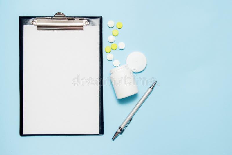 Odgórny widok pusty papier dla pisać doktorskiej recepcie Pigu?ki na b??kitnym tle obrazy stock