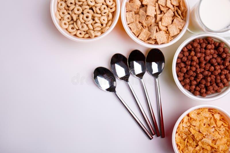 Odgórny widok różni typ cornflakes, w talerzach, cztery łyżki w prawym kącie, jest dojny zdjęcia royalty free