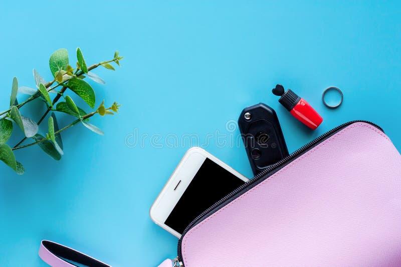Odgórny widok różowej damy torba z smartphone, samochodu kluczem, czerwoną pomadką, pierścionkiem i dekorującym kwiatem na błękit zdjęcia stock