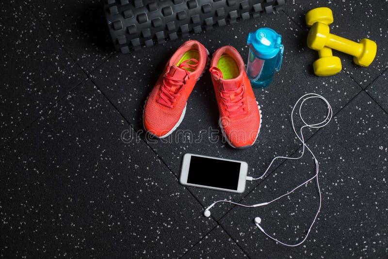 Odgórny widok różowi trenery, butelka dla wody, telefon i mali dumbells na czarnym tle, Bawi się akcesoria zdjęcie stock