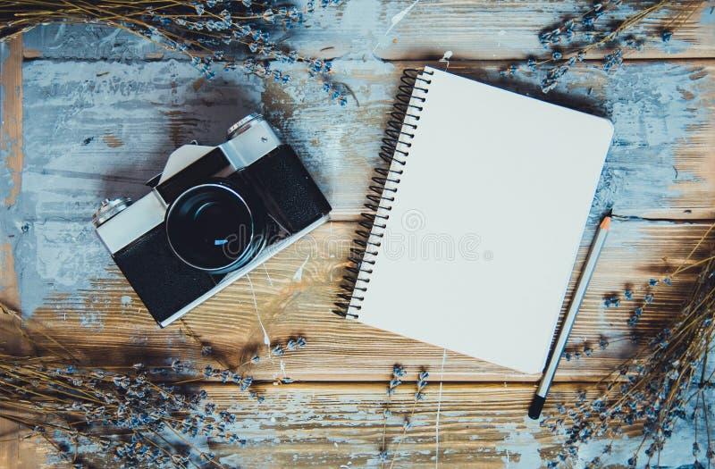 Odgórny widok retro kamera, lawendowy bukiet i notatnik na brązu drewnianym textured tle, fotografia royalty free