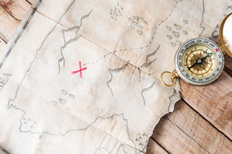 Odgórny widok rocznik imitaci skarbu mapa z czerwonym krzyżem i kompas na drewnianym biurku obrazy royalty free