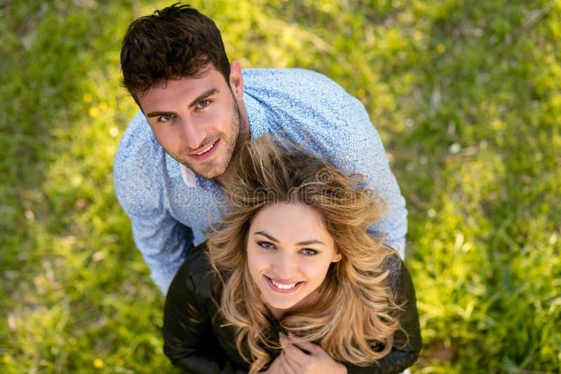 Odgórny widok rozochocona para, stać bosy w trawie patrzeje kamerę fotografia stock