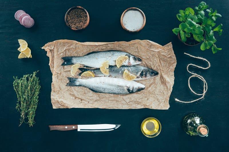 odgórny widok smakosz ryba z cytryna plasterkami na pieczenie pikantność i papierze obraz royalty free