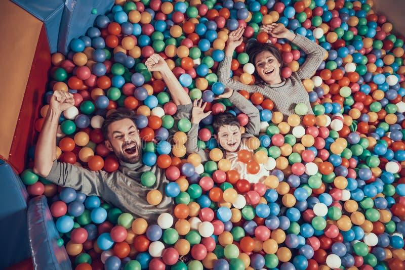 Odgórny widok Szczęśliwy rodzinny lying on the beach w basenie z piłkami obrazy stock