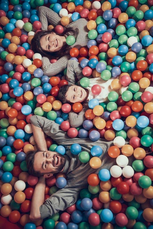Odgórny widok Szczęśliwy rodzinny lying on the beach w basenie z piłkami fotografia stock