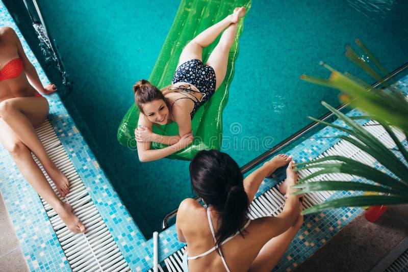 Odgórny widok szczupli młodzi żeńscy przyjaciele relaksuje przy hotelowym pływackim basenem obrazy royalty free
