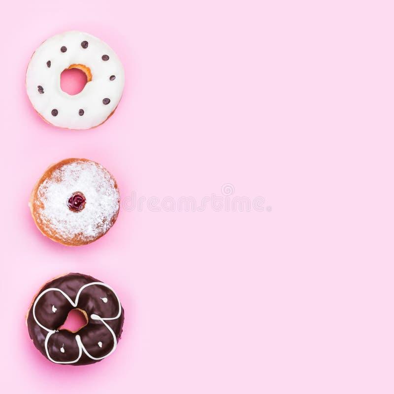 Odgórny widok trzy donuts różnego rodzaju odizolowywającego na różowym tle, kopii przestrzeń obraz royalty free