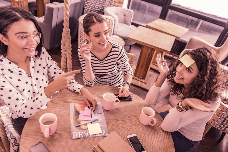 Odgórny widok trzy młodego freelancers spotyka na weekendzie i bawić się szarady obrazy royalty free