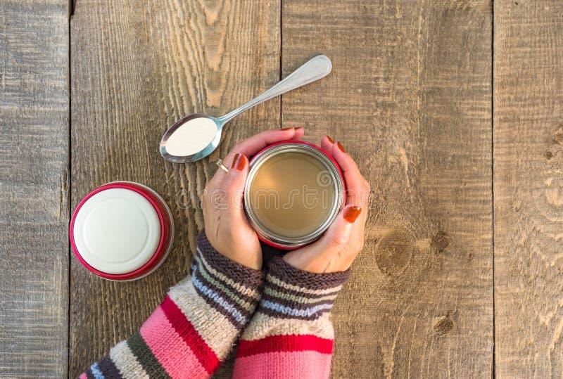 Odgórny widok trzyma kawowego kubek w rękach na nieociosanym kraju kobieta fotografia stock