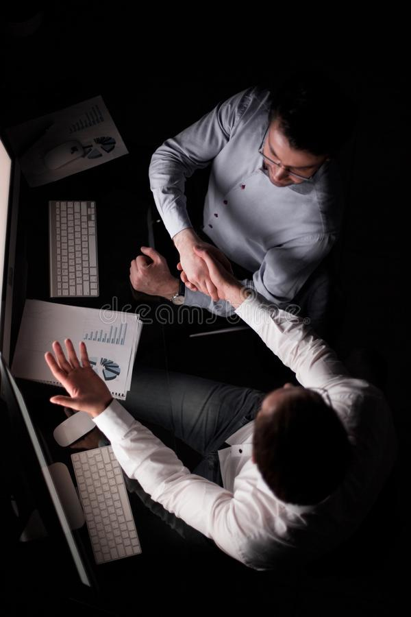 Odgórny widok Uścisków dłoni koledzy siedzi przy biurkiem zdjęcia stock