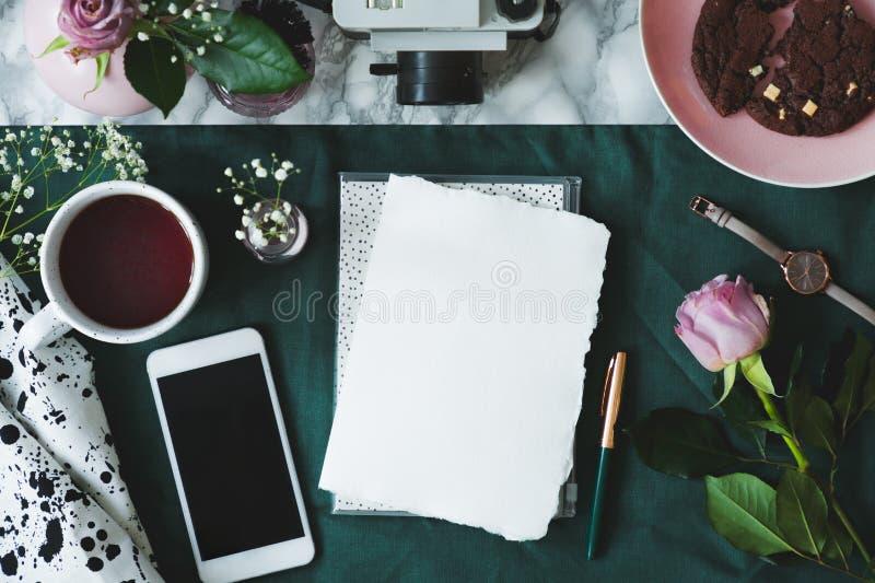 Odgórny widok umieszczający obok pustego papieru na marmurowym biurku z zielonym płótnem z pustym parawanowym telefonem, filiżank obrazy royalty free