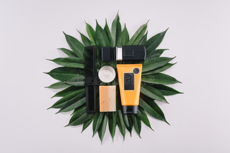 odgórny widok ustaweni fryzjerów męskich narzędzia na zielonych liściach zdjęcia royalty free