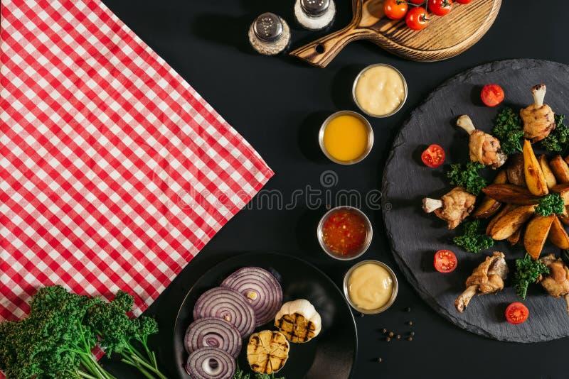 odgórny widok w kratkę pielucha, warzywa, kumberlandy i wyśmienicie piec grule z kurczakiem na czerni, obrazy royalty free