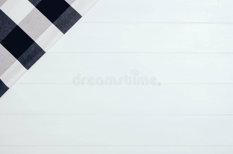 Odgórny widok w kratkę sukienna pielucha na białym drewnianym stole zdjęcie royalty free