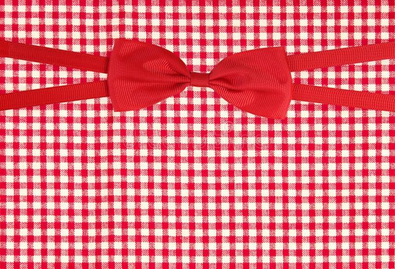 Odgórny widok wiązany czerwony tasiemkowy łęk na firebrick gingham wzoru tekstury tle, opakunku prezenta pudełko zdjęcie royalty free