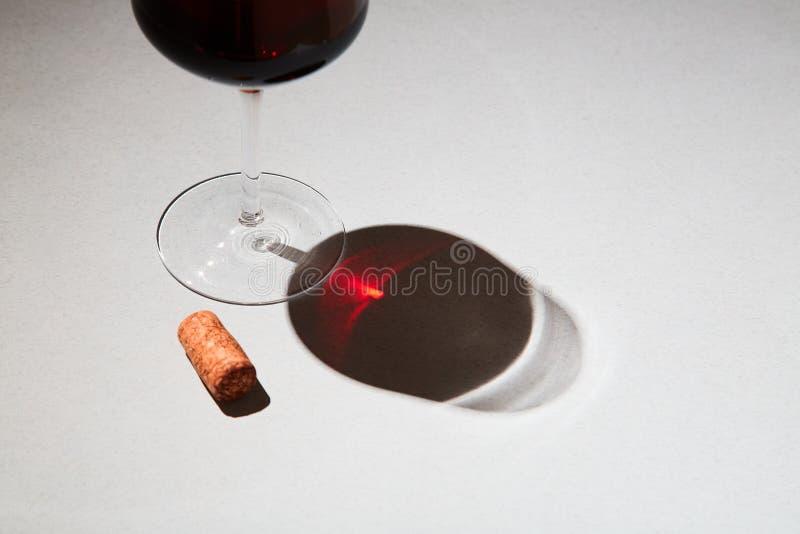 Odgórny widok wiązka winogrona na czerń łupku desce z błyszczącym szkłem czerwone wino i rozmaryny kapuje na kolorowym tle zdjęcie royalty free
