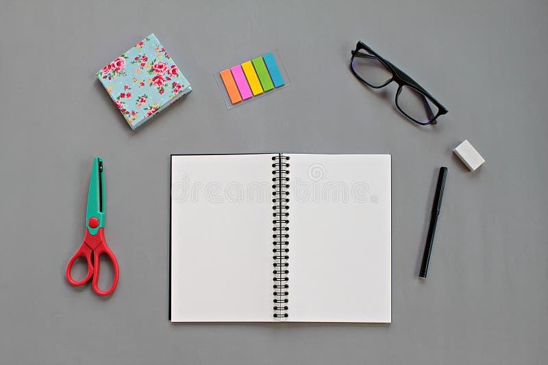 Odgórny widok workspace biurko z pustym notatnikiem i biuro materiały ustawiającymi na szarym tle zdjęcie stock