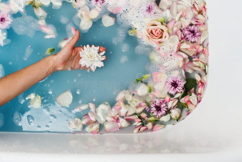 Odgórny widok wypełniający z błękitnymi bąbli płatkami z kobiety ręką i wodą skąpanie zdjęcie royalty free