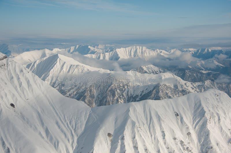 Odgórny widok wysokie czyste zim góry zakrywać z śniegiem pod jaskrawym niebieskim niebem fotografia royalty free