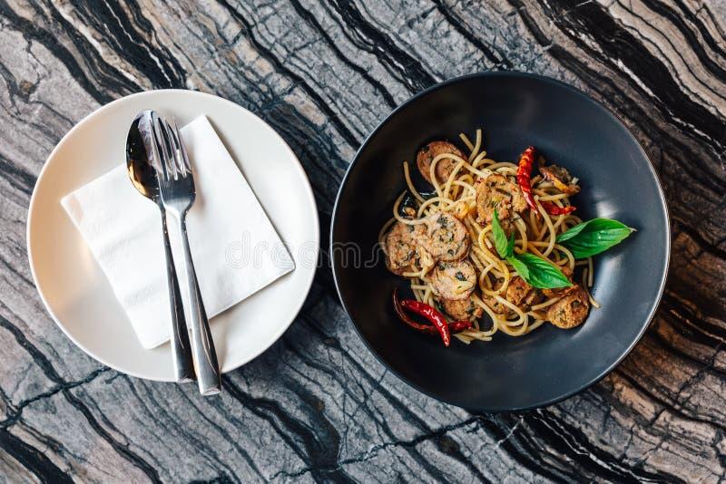 Odgórny widok Wysuszony spaghetti Chili Sai Ua i Północny Tajlandzki Kiełbasiany przepis słuzyć w czarnym talerzu z bielu cutlery zdjęcie stock