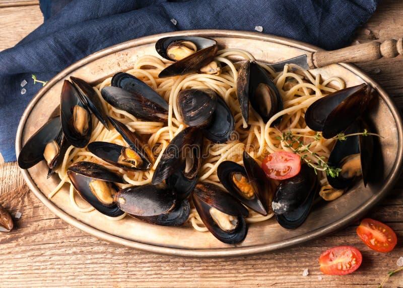Odgórny widok złoty talerz z włoskim makaronem, mussels, rżnięci czerwoni pomidory i zieleni rozmaryny, obrazy stock