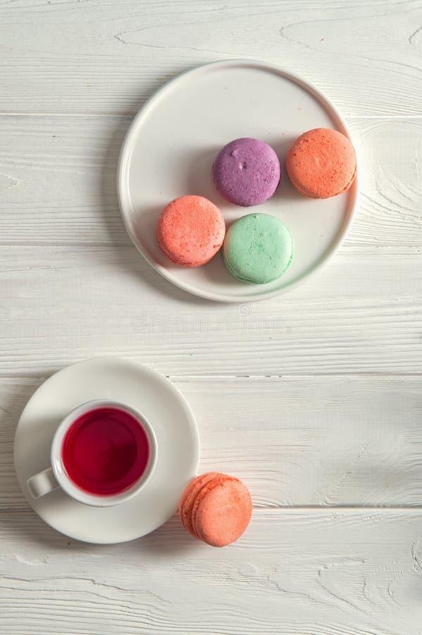 Odgórny widok z bliska Provence śniadaniowi Pastelowi francuscy macarons na round talerzu, filiżanka jagodowa herbata, nieociosan zdjęcia royalty free