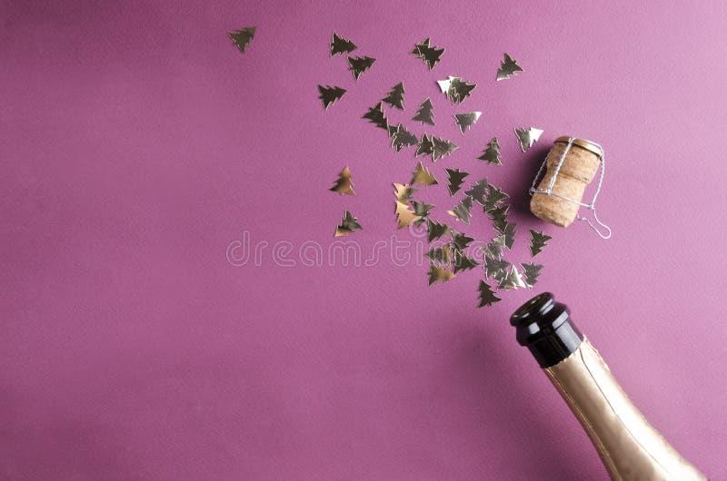 Odgórny widok zakorkowana butelka szampańscy i błyszczący złoci confetti na purpurach ukazuje się obrazy royalty free
