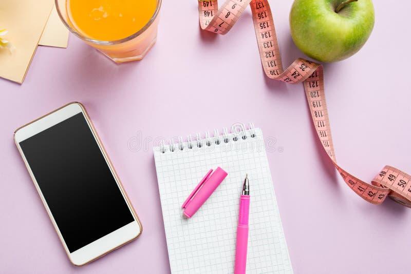 Odgórny widok zielony jabłko, pomiarowa taśma, telefon komórkowy, pióro i otwarty notatnik, koncepcja kulowego fitness pilates zł zdjęcia royalty free