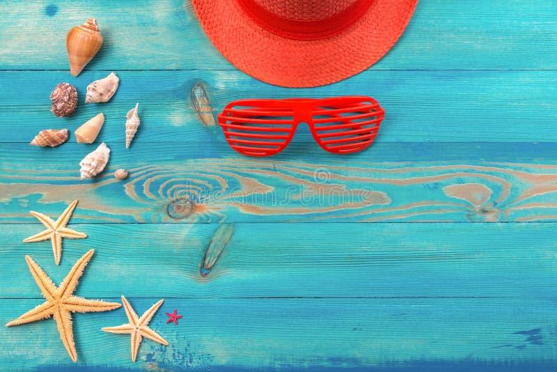 Odg?rny widok na ?ywym koralowym koloru kapeluszu, louvered okularach przeciws?onecznych, seashells i rozgwiazdzie na b??kicie, m zdjęcie stock