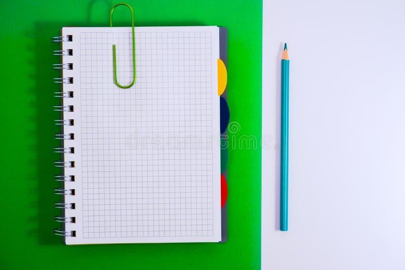 Odg?rny widok otwarty ?limakowaty pusty notatnik z o??wkiem na zielonym biurka tle obrazy royalty free