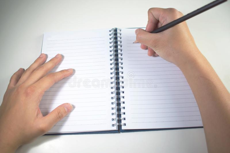 Odg?rny widok Ręka pisze książce z czarnym ołówkiem zdjęcia stock