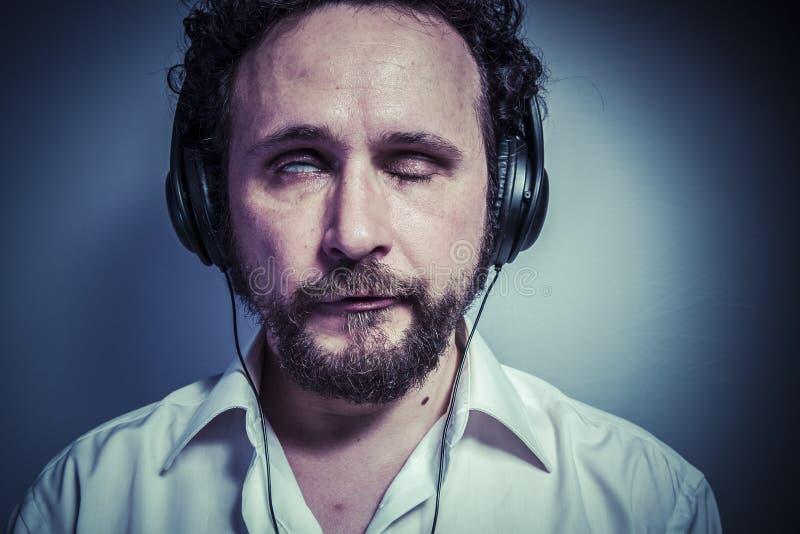 Odi la musica, l'uomo con l'espressione intensa, camicia bianca fotografia stock