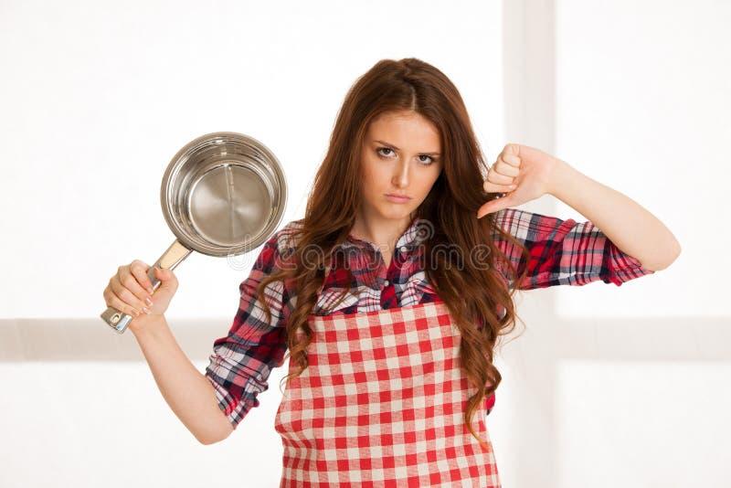 Odio hermoso de la mujer que cocina mostrando el pulgar abajo foto de archivo libre de regalías