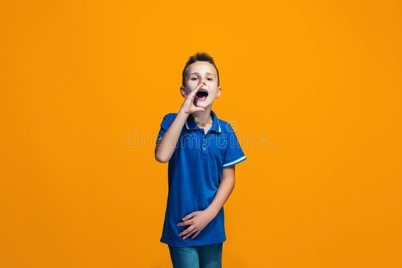 Odizolowywający na pomarańczowej młodej przypadkowej nastoletniej chłopiec krzyczy przy studiiem obrazy stock