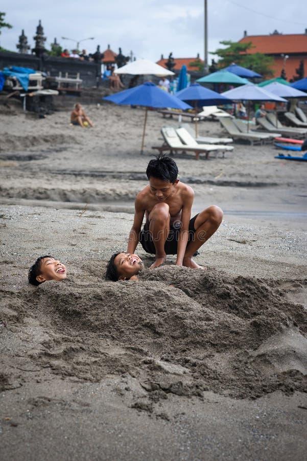 Odkrywa Indonezja Radośni balijczyków dzieci śmia się bawić się z czarnym piaskiem Canggu, Bali, Indonezja, 24 2016 Wrzesień zdjęcia royalty free
