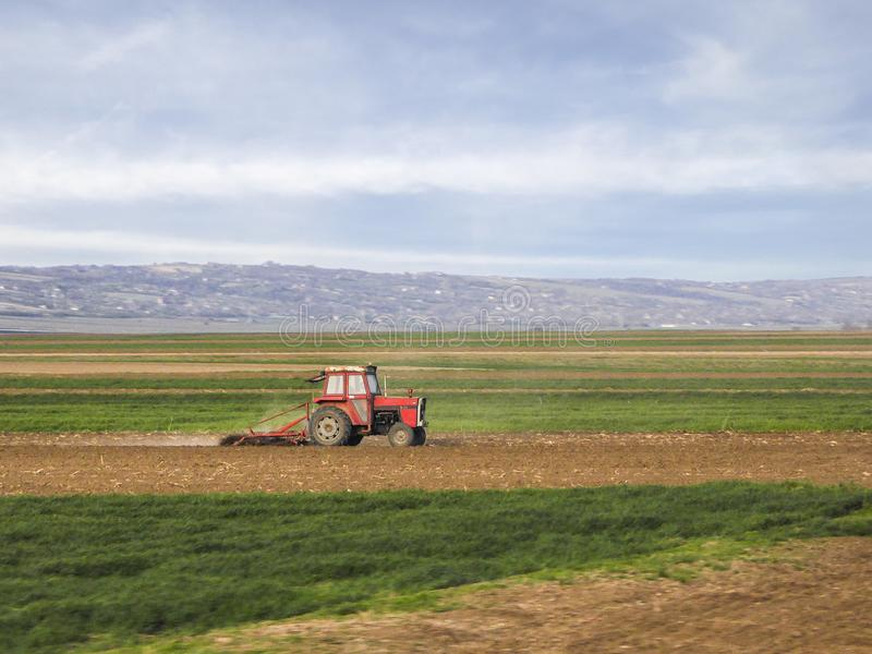 Odla traktoren i fältet - vårtid arkivbild