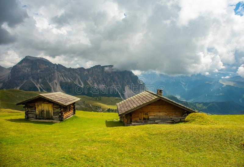 Odle Puez mountain and wooden chalets in Dolomites, Trentino Alto Adige, Italy. Summer view of Seceda Odle Puez mountain and wooden chalets in Dolomites royalty free stock photo