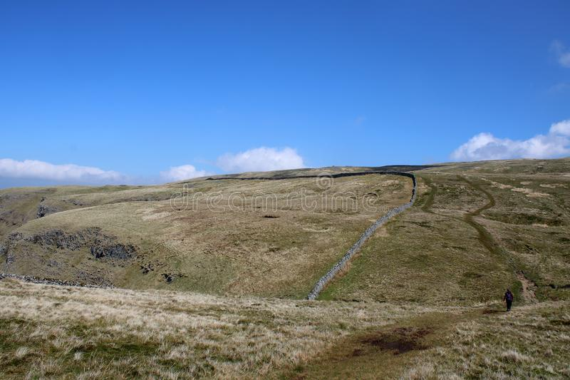 Odległy piechur na szorstkim moorland footpath, Cumbria fotografia stock