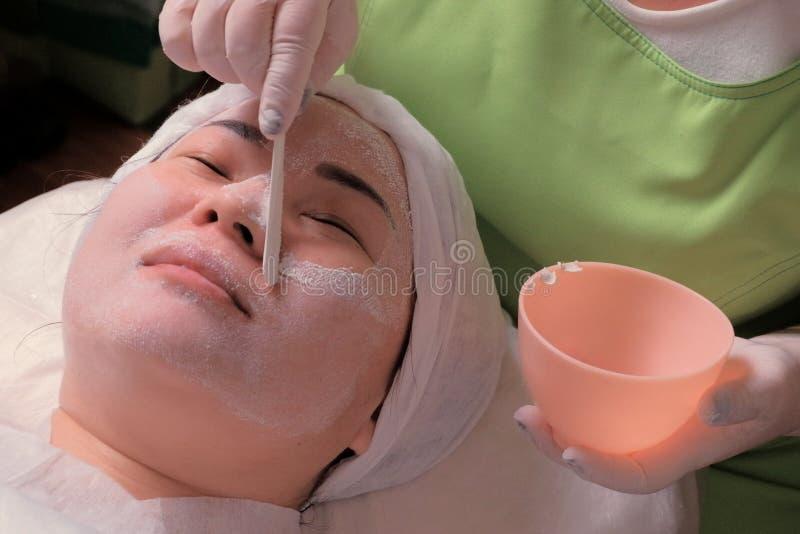 Odmłodnieć cosmetological skórę czyści procedurę Ręki beautician w białych rękawiczkach z kosmetycznym kijem usuwają obraz royalty free