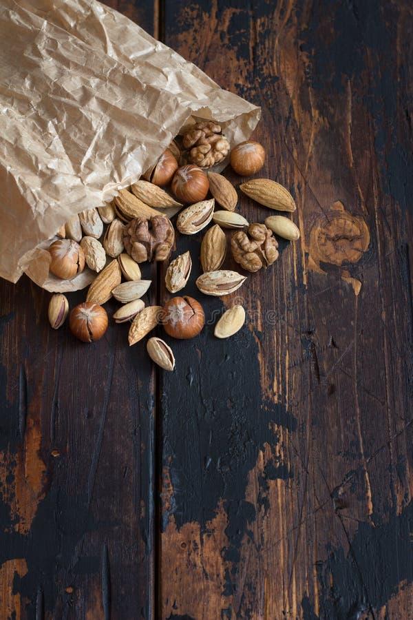 Odmiana orzechów w opakowaniu nad drewnianym stołem migdały, orzechy włoskie, orzechy leszczyny, pistacje obraz stock