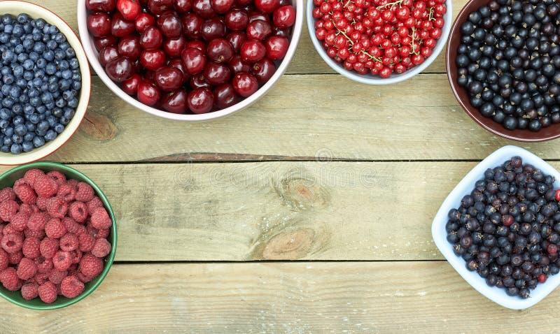 Odmiany świeżych owoców ogrodowych i jagód leśnych: malina, borówka, porzeczka czerwona i czarna, czereśnie na drewnianej zakładc obraz royalty free